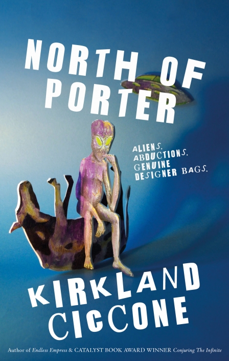 Kirkland Ciccone's book cover for 'North of Porter' published by Strident Publishing. The cover is showing a cut out allien sat on an upside down cut out cow. In the background there is a flying saucer. The cover in blue, green & purple. Artwork, photography & design by Ida Henrich