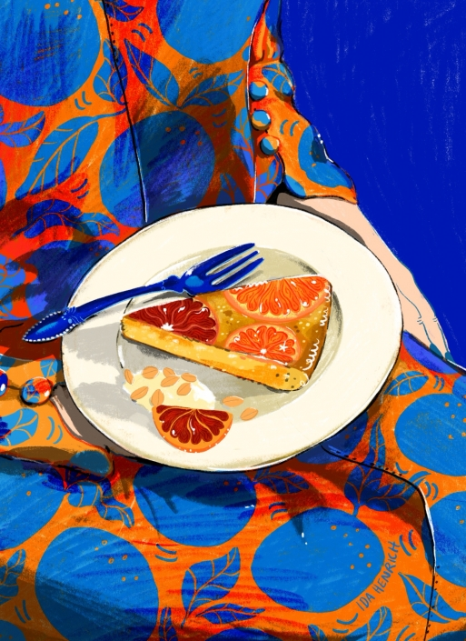 Orange cake on the lap of a woman with an orange pattern dress. Image by Ida Henrich